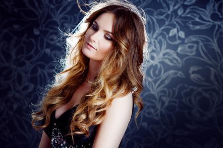mooi meisje met lang bruin gekruld haar, donkere achtergrond Stockfoto
