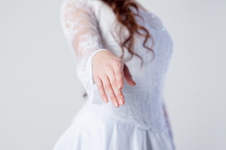 The bride extends her hand,  woman in a wedding dress photo