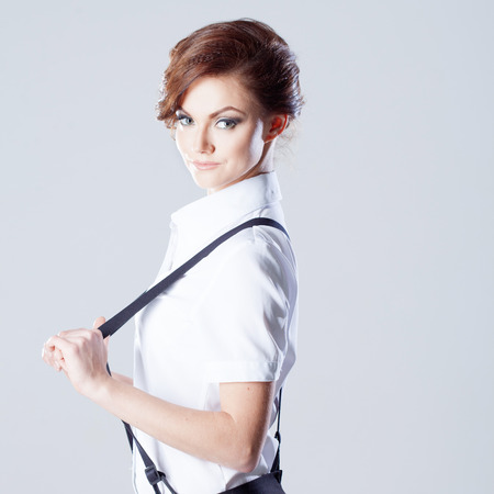 suspenders: Successful business woman, pulls suspenders and looking into the frame Stock Photo