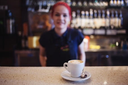 automat: girl Barista gives coffee  to the customers