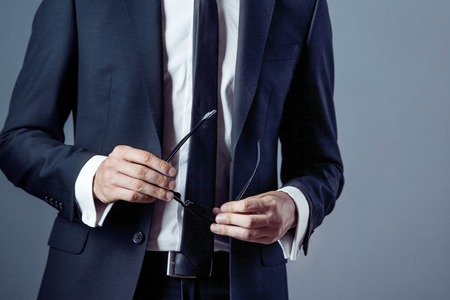 businessman suit: man in suit on a grey background