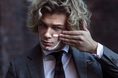 사업가 전사. 젊은 남자가 그의 얼굴에 전쟁 페인트를 만든다. 스톡 콘텐츠