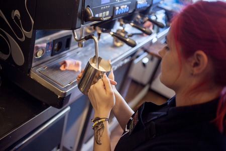 automat: young girl Barista prepares coffee in restaurant Stock Photo