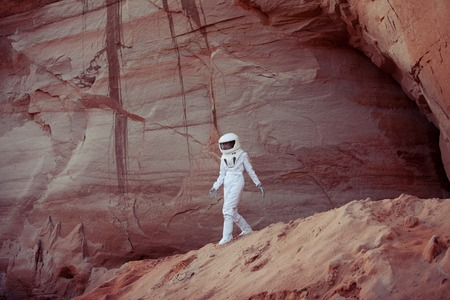 inhabited: futuristic astronaut on another planet, sandy red planet Stock Photo