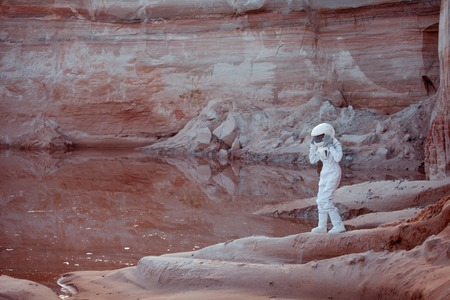 discoverer: futuristic astronaut on another planet, sandy red planet Stock Photo