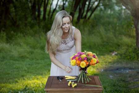 site preparation: Young beautiful woman florist. The girl in the Park draws a bouquet Stock Photo