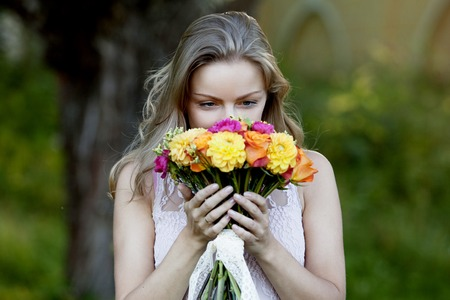 Young beautiful woman with a bright bouquet of flowers