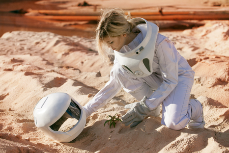 futuristic astronaut on another planet, sandy red planet 免版税图像