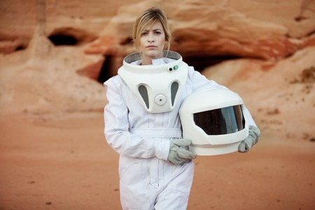 future: futuristic astronaut on another planet, sandy red planet Stock Photo
