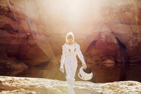 colonization: futuristic astronaut on another planet, sandy red planet Stock Photo