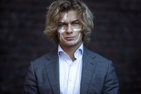 viking: Businessman warrior. Young man makes war paint on his face