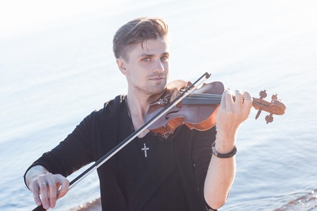 violin player: Violinist playing a violin, on the background of the sea