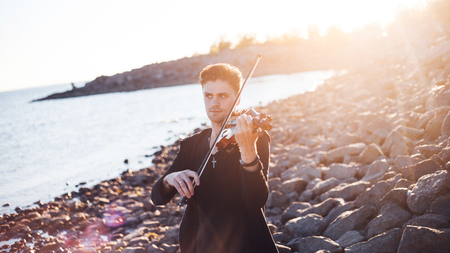 violinist: Violinist playing a violin, on the background of the sea