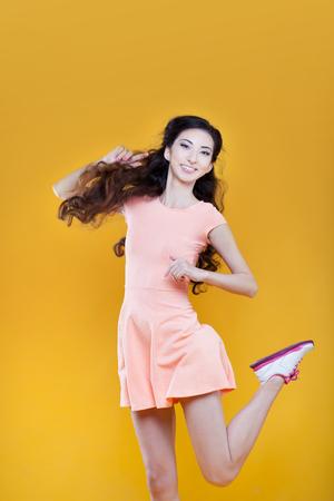 niñas sonriendo: Moda niña asiática. Retrato en el fondo amarillo. Foto de archivo