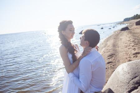 manos sosteniendo: Just married couple running on a sandy beach