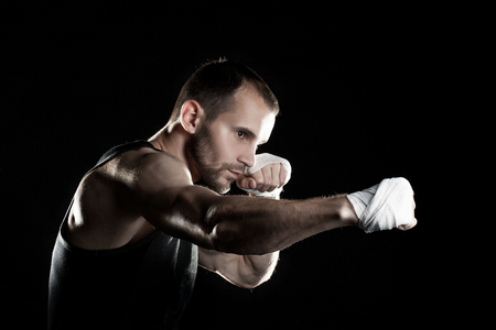 clasps: muscular man on a black background, clasps hands in a fist