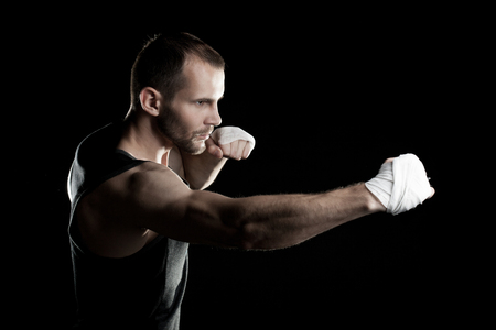 patada: muscular hombre sobre un fondo negro, agarra las manos en un puño Foto de archivo