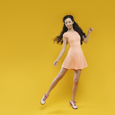 Fashion asian young  girl. Portrait on the yellow background.