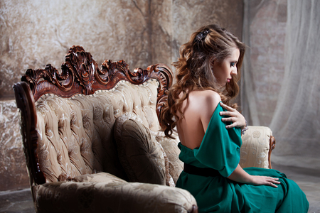 green couch: young beautiful woman in long dress against the wall