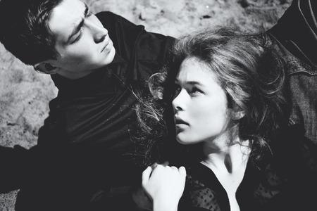 美しいカップル。女の子の若い男が、黒と白の肖像画の耳元で何かささやき