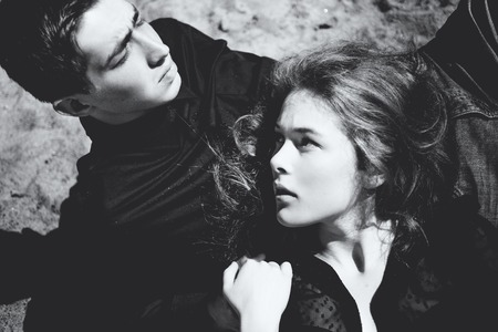 Beautiful couple. Girl whispers something in the ear of the young man, black and white portrait