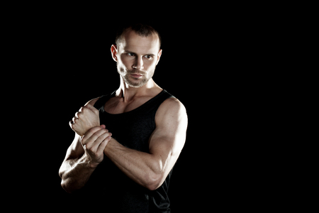 man power: muscular man on a black background, clasps hands in a fist