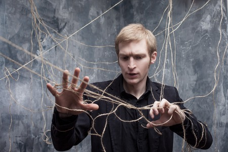 powerless: Young man in a black suit got caught in the web.