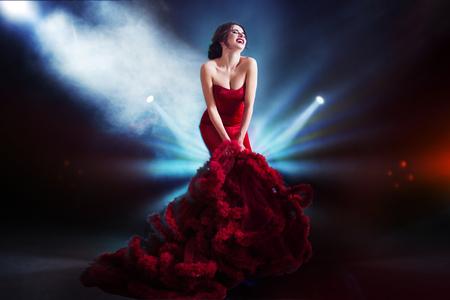 Mujer Modelo de la belleza morena de vestido rojo de noche. Hermosa maquillaje de lujo de la moda y el peinado