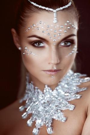 bellezza donna trucco con cristalli sul fronte su sfondo nero