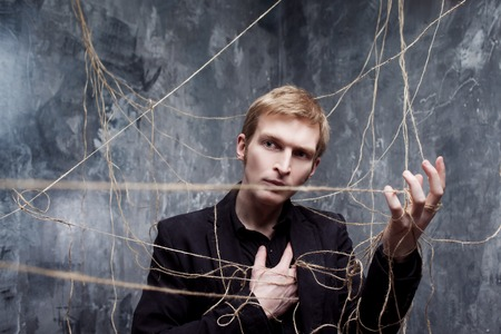 puppet master: Young man in a black suit got caught in the web.
