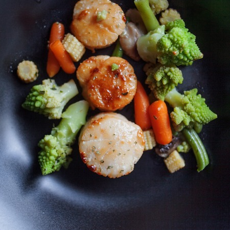 st jacques: Sea Scallops with vegetables on a black plate. Seafood.