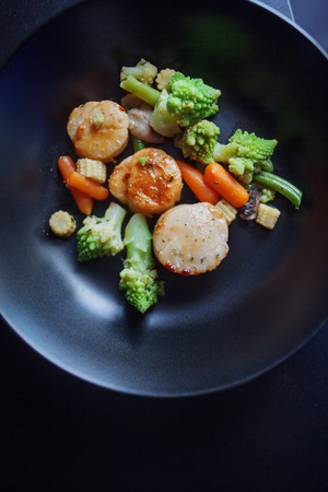 flesh eating animal: Sea Scallops with vegetables on a black plate. Seafood.