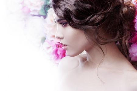 甘くて官能的な美しいファッションの少女の肖像画。美しい化粧と乱雑なロマンチックな髪型。花の背景。