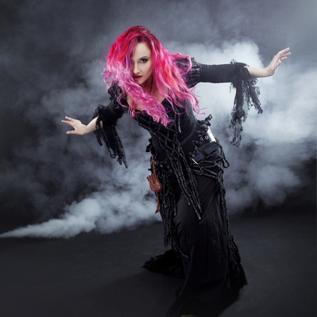 Attractive woman with red hair in witches costume Stock Photo