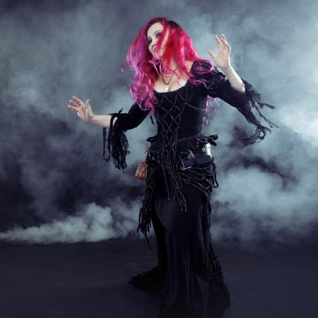 curse: Attractive woman with red hair in witches costume Stock Photo