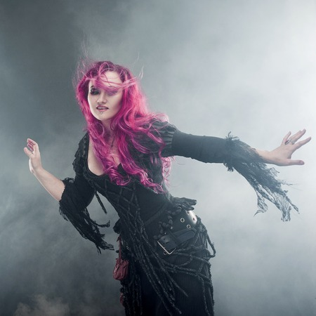 Attractive woman with red hair in witches costume