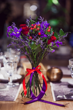 Flowers composition in restaurant, the small roses and irises, a combination of red and purple.