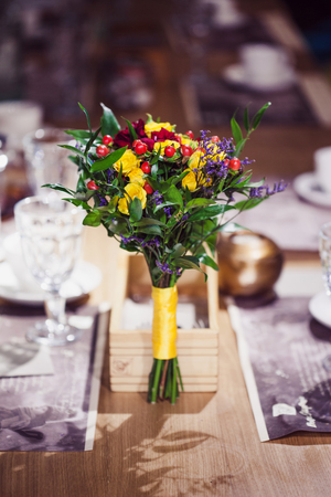 Flowers composition in restaurant, roses and irises, combination of shades of purple