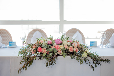 Flower arrangement on the table. Flowers on a white tablecloth, roses and peonies Stock Photo