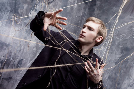 restrain: Young man in a black suit got caught in the web.