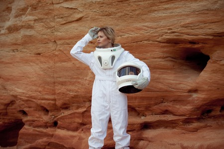 futuristic astronaut on another planet, sandy red planet Фото со стока - 60692454