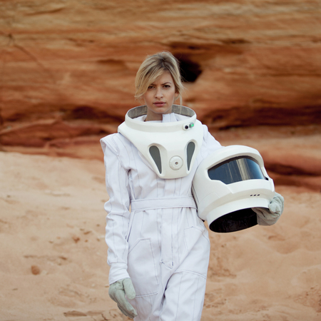 another: futuristic astronaut on another planet, sandy red planet Stock Photo
