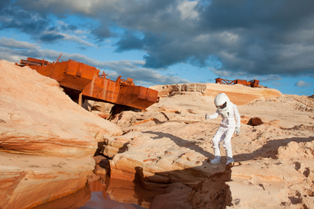 dry suit: futuristic astronaut on another planet, sandy red planet Stock Photo