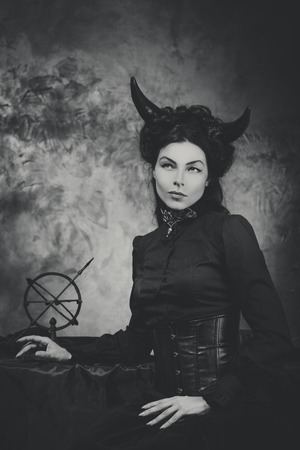 succubus: Black and white retro photo, woman demon. Girl with horns, effect of toning Stock Photo