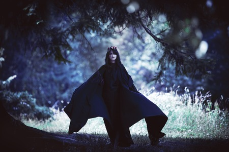 young black-haired girl in a long black cloak with a hood in a dark forest