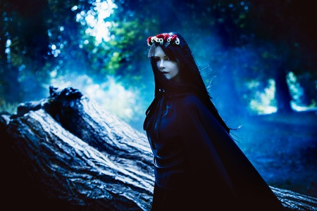 어두운 숲의 후드와 함께 긴 검은 망토 젊은 검은 머리 소녀