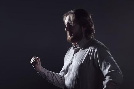 man profile: Man with a beard, profile on a dark background.