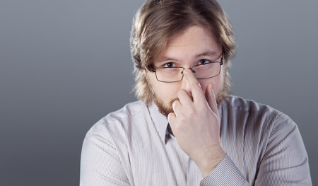 humorously: The bearded young man adjusts his glasses Stock Photo