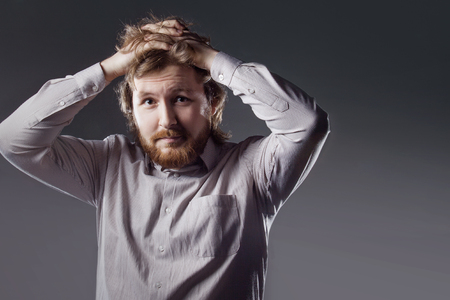 humorously: Portrait of bearded young man who grabs his head.