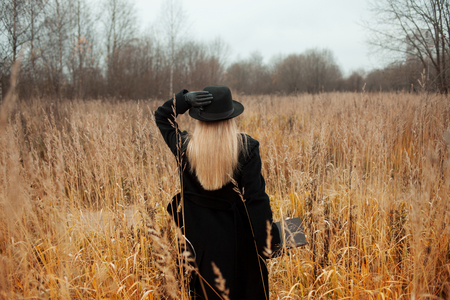Portrait of young attractive woman in a black coat and hat. Shes one in a field reading a book, autumn landscape, dry grass